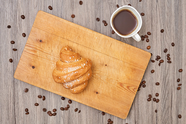 Top view of homemade croissant and hot black coffee on wooden table