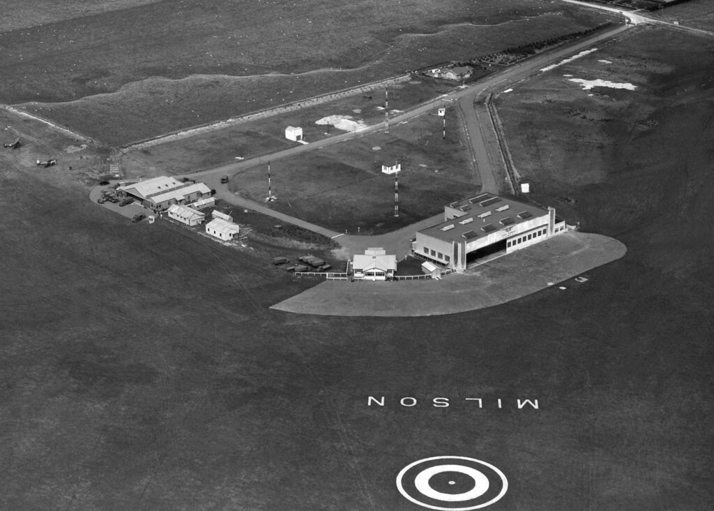 1942 RNZAF Station Milson, (Palmerston North) showing the Union Airways hangar to the right and three RNZAF Hawker Hind aircraft on the field on the left beside the RNZAF hangar.