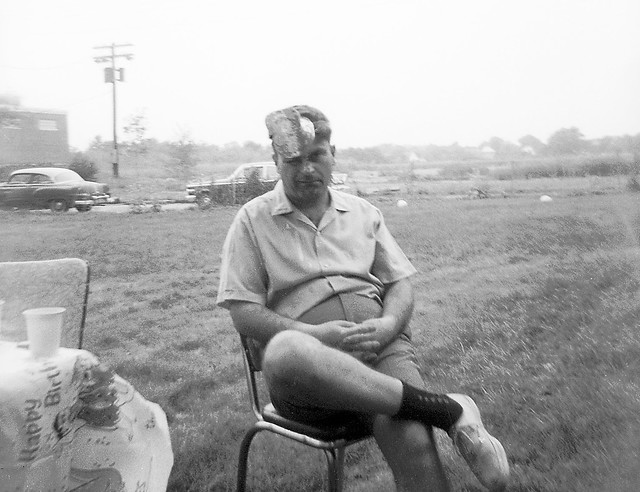 Dad wearing a pointy hat at my sister's 5th birthday party. His 1953 Pontiac Chieftain parked on Rock St In the background. The new Surf Club was building their parking lot in what used to be a salt marsh. Milford CT July 1967