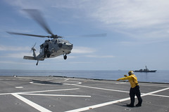 SOUTH CHINA SEA (July 9, 2021) A Sailor aboard the littoral combat ship USS Tulsa (LCS 16) directs and MH-60S Sea Hawk from Helicopter Sea Combat Squadron (HSC) 21 during flight operations while sailing with the guided missile destroyer USS Kidd (DDG 100). Tulsa, part of Destroyer Squadron 7, is on a rotational deployment, operating in the U.S. 7th Fleet area of operations to enhance interoperability with partners and serve as a ready-response force in support of a free and open Indo-Pacific region. (U.S. Navy photo by Mass Communication Specialist 3rd Class Chase Stephens)