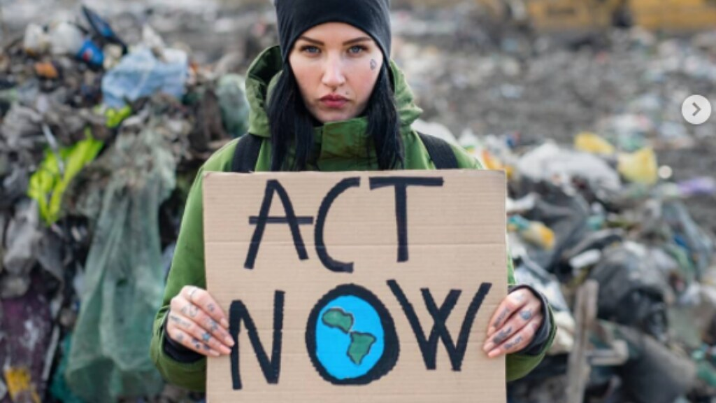A photo of a young person holding up a sign that says 'Act Now'