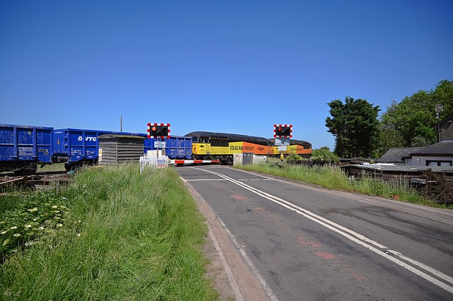 Hired in Colas Grids 56105 & 56049 passing throught the big fenland landscape at the head of 6Z28, 07.10 Chaddesden Sdgs - Brandon Down Sdgs, with the loaded stone, passing over Mile End Xing, Prickwillow. 09 06 2021