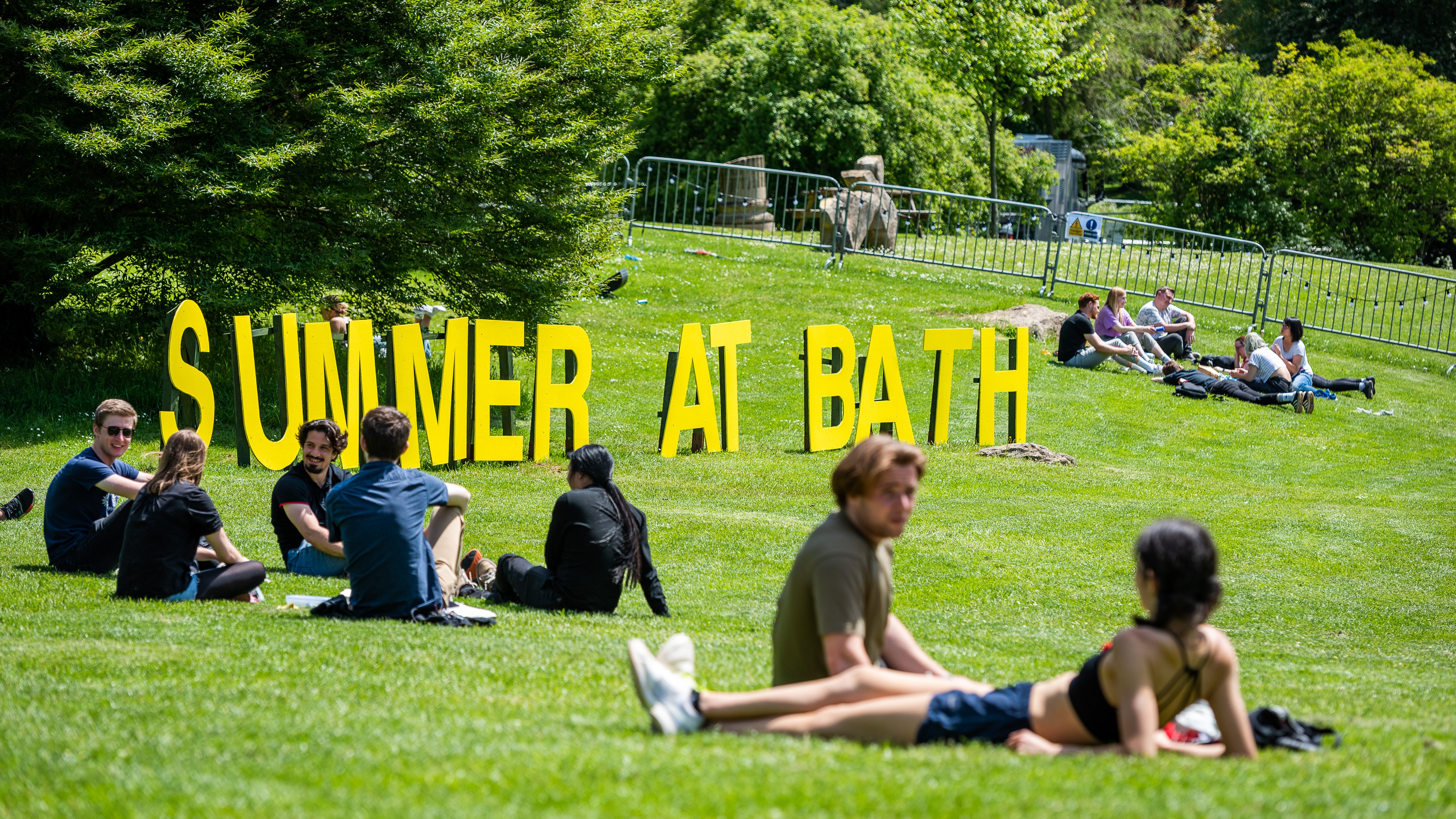 The words 'summer at Bath' in big yellow capital letters by the campus lake as part of the 'Summer at Bath' programme of events