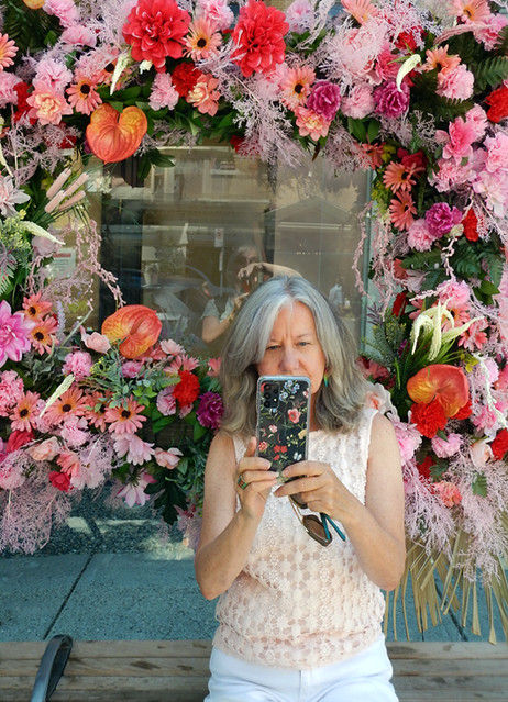 My friend, looking very floral herself, at a bus stop during the Fleurs de Ville: Rosé, a floral walk of various pinks, done in support of breast cancer research