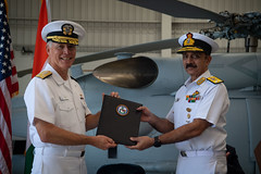 Vice Adm. Kenneth Whitesell presents the Material Inspection and Receiving Report for the Indian Navy's first MH-60R to Vice Adm. Ravneet Singh. (U.S. Navy/MC2 Sara Eshleman)