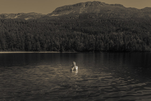 Woman in the lake of Sandvatn in front of the mountain of Blefjell, Norway