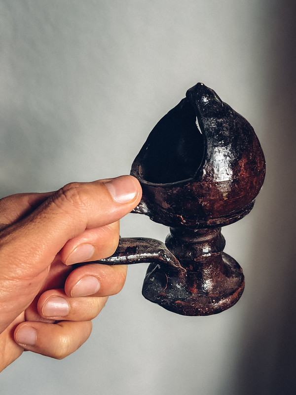 A ceremonial lamp for religious rites in a person's hand