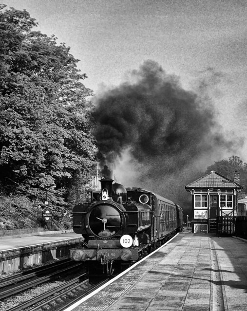 Former GWR pannier tank L90, in London Transport livery, blasts through Chorleywood station with a Harrow to Amersham passenger train during a Steam on the Met event on 23rd May 1993.