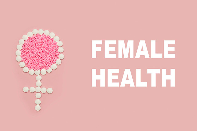 Female health and sign on bright colored background