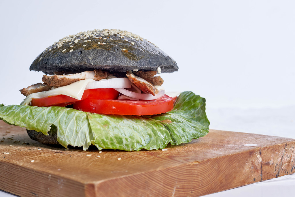 Black hamburger with juicy meat, tomato, onion and cheese