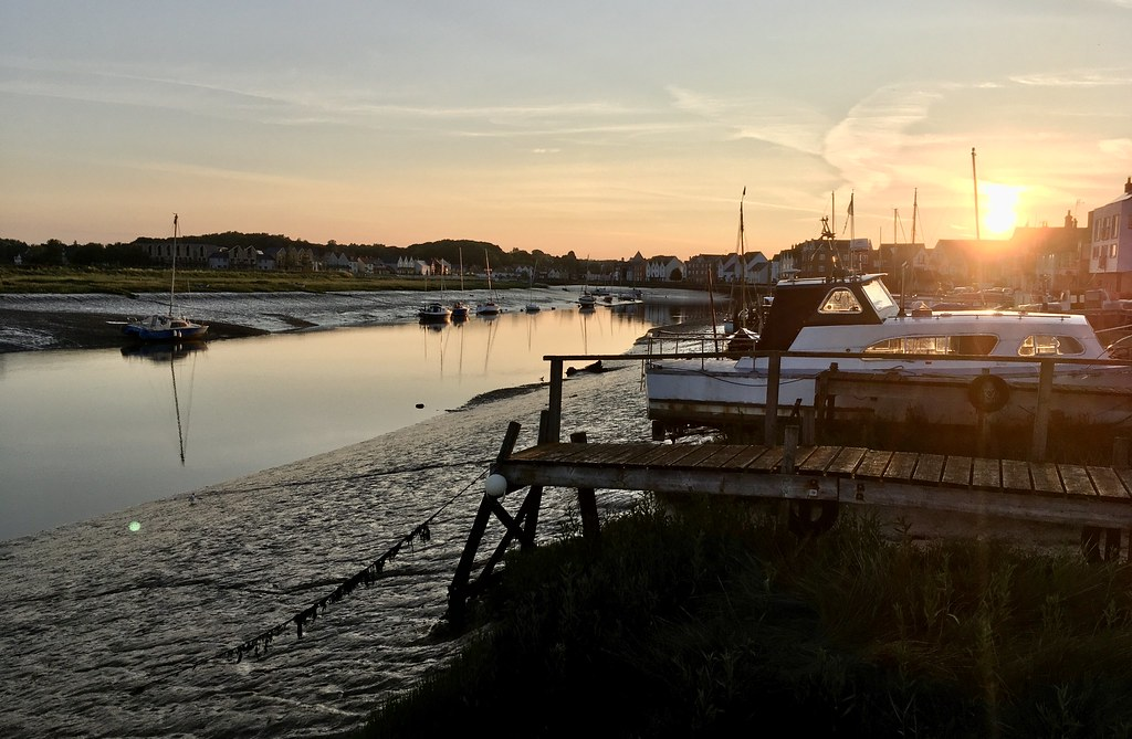 Photo of a river at low tide and sunset, with a wooden jetty stretching out over the mud, and small yachts moored on the other side