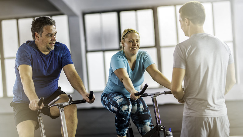 A man and woman in the gym, sitting on exercise bikes while talking to their personal trainer.