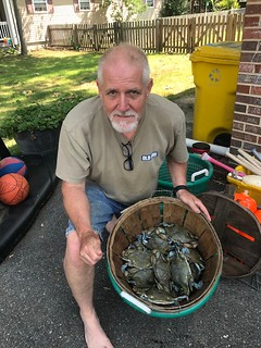 Photo of man with a basket of blue crabs