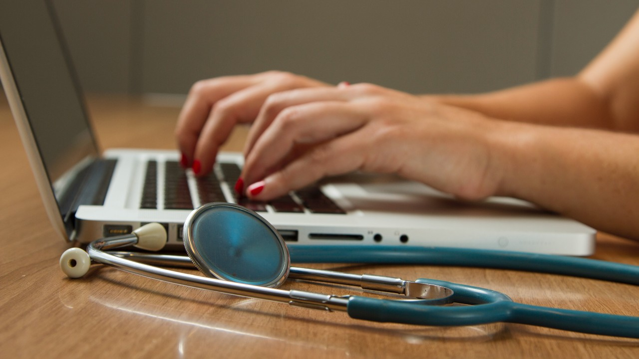A person typing on a laptop, with a stethoscope on the table next to them