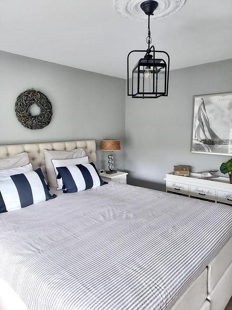 Landelijke slaapkamer bed met gecapitonneerd hoofdbord gestreepte kussens