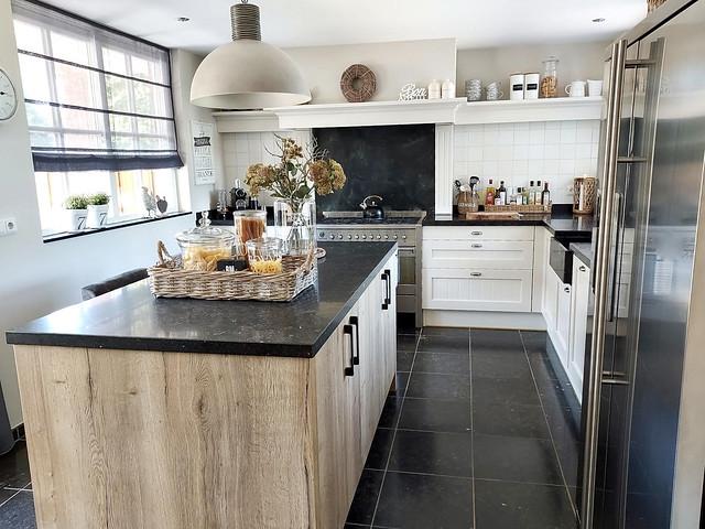 Landelijke witte keuken vouwgordijn keukenraam keukeneiland met ontbijtbar