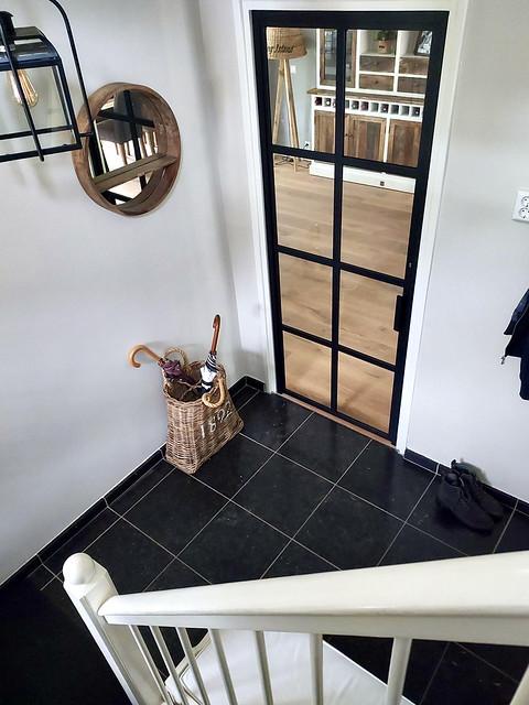 Zwarte tegelvloer witte muren landelijke hal stalen deur zwart