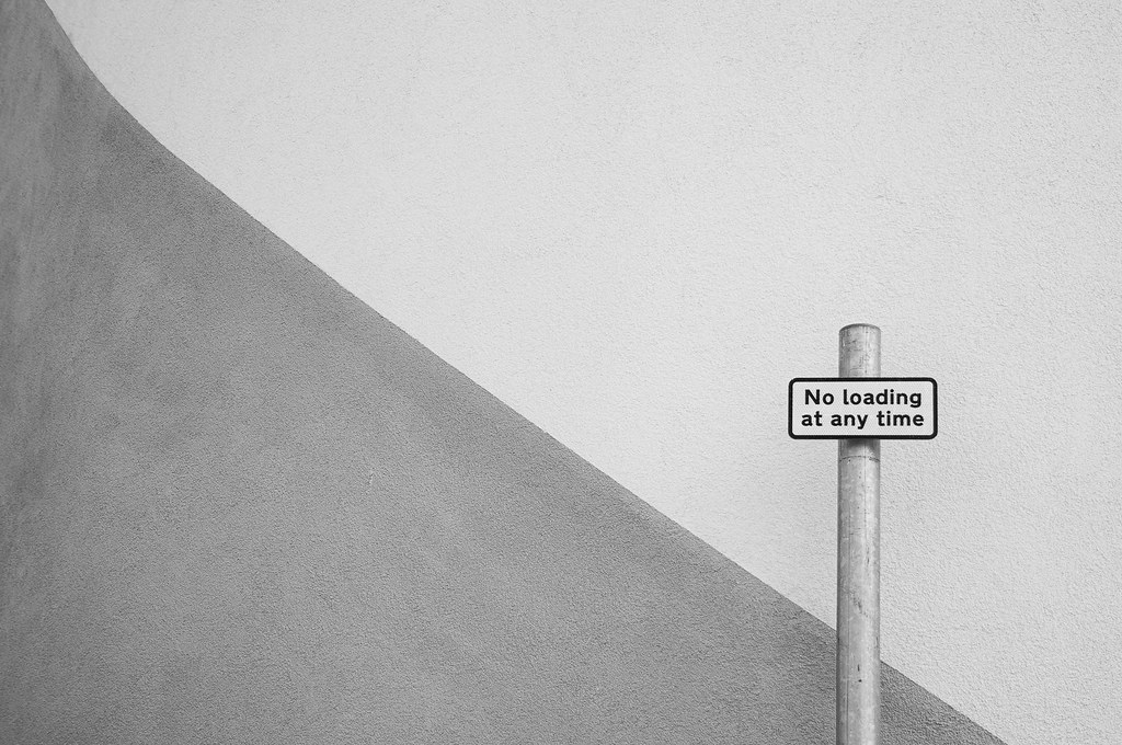 Black and white photo of sign saying No Loading At Any Time against a patterned wall