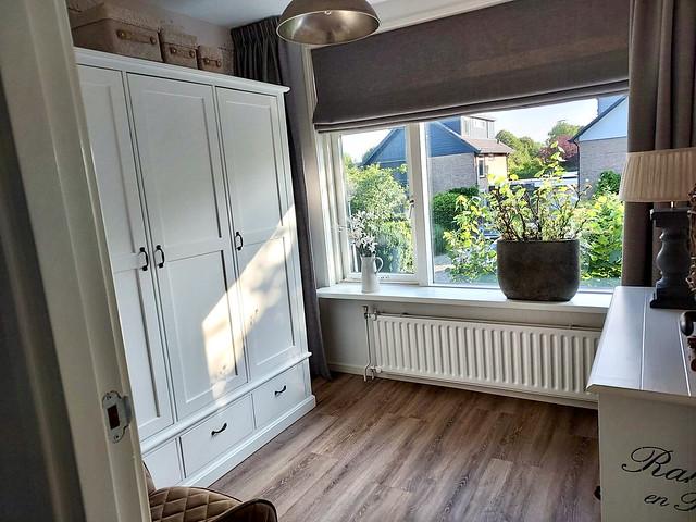 PVC vloer landelijke slaapkamer vouwgordijnen ovale pot met plant vensterbank