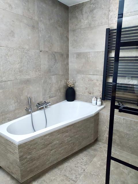 Bruingrijze badkamer wit ligbad zwarte badkamer radiator stalen deur