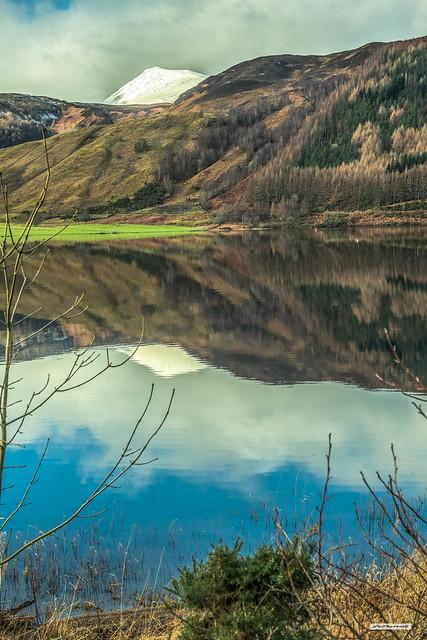 Glassy still Ceann Loch reflecting the snowy peak of Ben Tee, forest, pasture and moorland, Great Glen, Lochaber, Inverness-shire, Scotland.