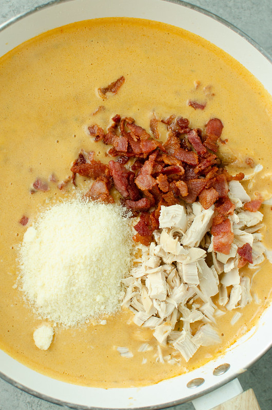 Spicy sauce in a white pot with crispy bacon, cooked chicken, and grated Parmesan on top