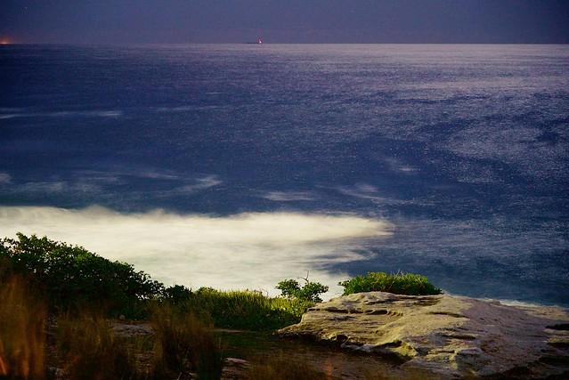 THE BEACH UNDER A BLOOD MOON NIGHT SKY.