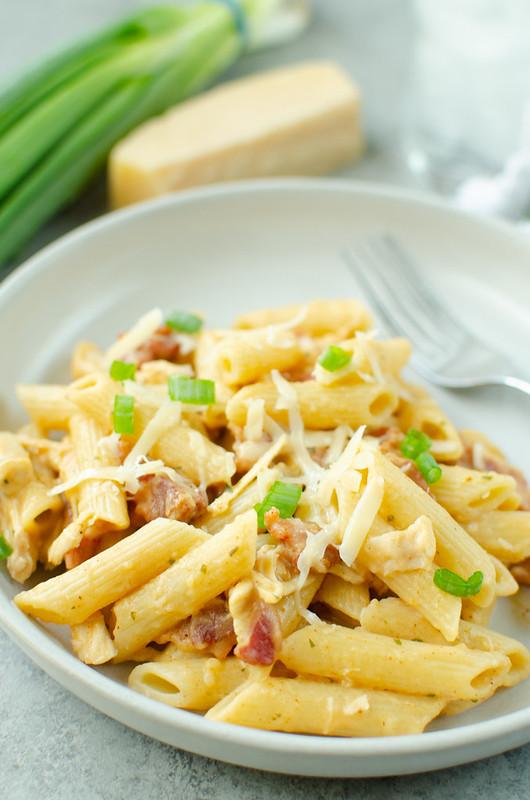 Spicy Bacon Ranch Pasta on a white plate white plate with a fork, parmesan wedge, and green onions in the background