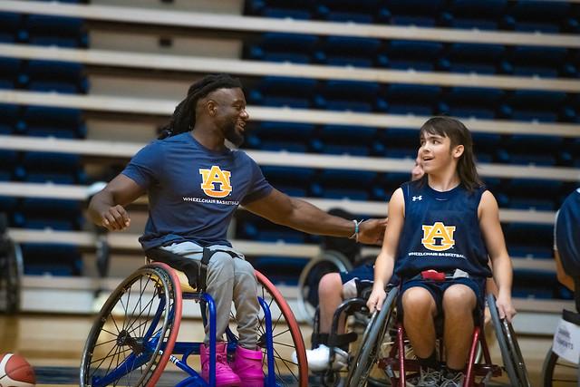 U.S. Paralympic Gold Medalist Matt Scott talks with an Auburn Wheelchair Basketball Summer Camp participant.