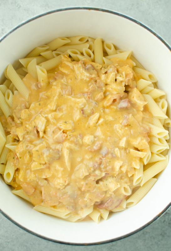 Spicy, cheesy sauce poured over penne noodles in a white pot