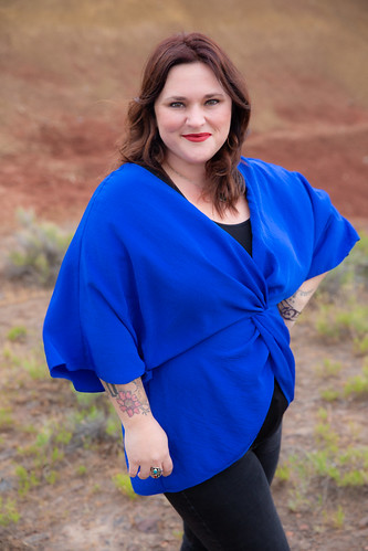 Author Kelly Lewis in a vibrant blue shirt against a natural background. From Read This: The Book That Will Inspire, Challenge, and Bring Joy