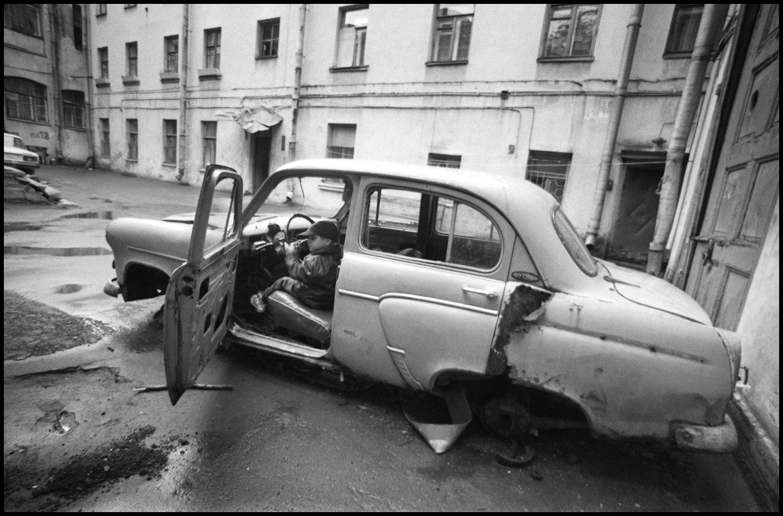 Дворы на Галерной. Мальчик в разбитой машине.