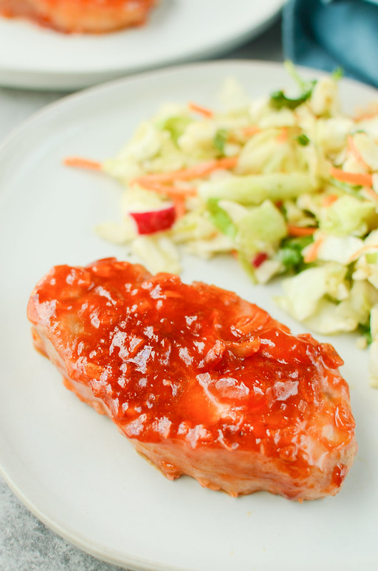 Boneless apricot pork chops on a white plate with salad in the background