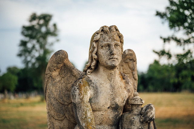 Statue of an angel at a cemetery with blurry background