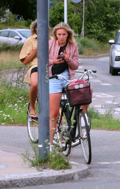 Using mobile phones while cycling is only permitted in Copenhagen when its hands free -  2 phone addicts take advantage of a red traffic light