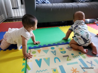 two babies on a playmat