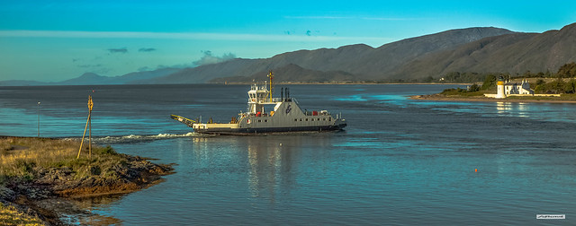 Corran Ferry on Loch Linnhe at its narrowest point. Beyond here it widens to 4 miles. Opposite Oban it reaches 10 miles across. After sunrise the sunlight catches the Lighthouse, Ferry-boat and its churning wake, Inverness-shire, Scotland.