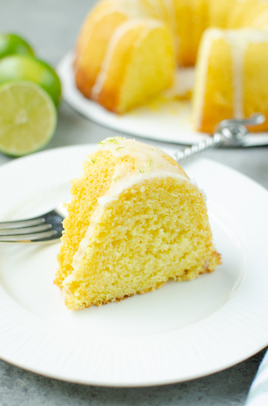 Slice of margarita bundt cake with glaze and lime zest on top; on a white plate with a fork. Limes and the rest of the cake in the background