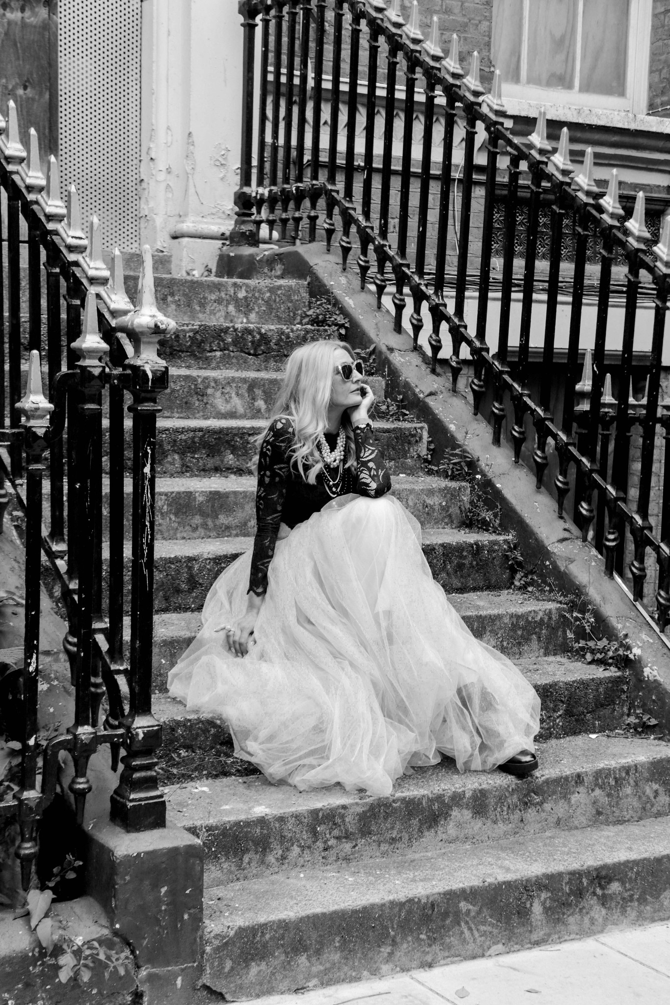 Giles Caldicott Photography: Catherine Summers AKA Not Dressed As Lamb   Wearing: cropped, long sleeve black lace top, pearl-effect square sunglasses, nude tulle maxi skirt, black lace-up boots   Sitting on the steps leading up to a boarded-up abandoned London town house
