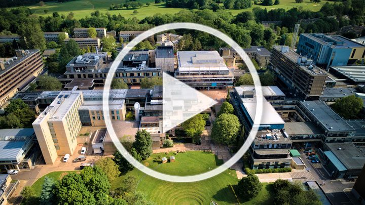 Video play button over aerial campus shot