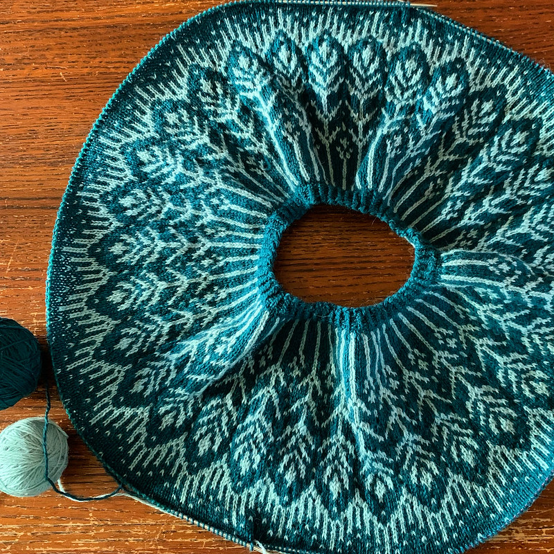 Colorwork yoke of a Sonrae sweater in shades of green, laid out flat in a circle on needles