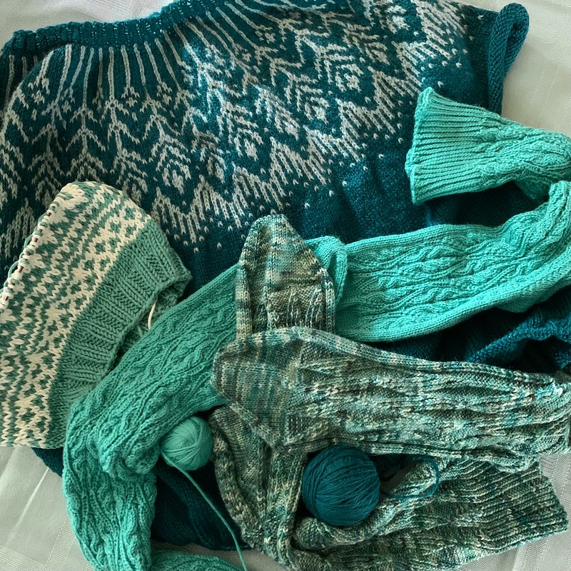 Stack of knitting projects in progress (WIPs) in various shades of green