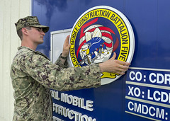 OKINAWA, Japan (July 26, 2021) Builder Constructionman Tyler Stewart, assigned to Naval Mobile Construction Battalion (NMCB) 5, hangs the battalion's logo before a relief-in-place/transfer-of-authority ceremony onboard Camp Shields, Okinawa, Japan, July 26. U.S. Navy Seabees assigned to NMCB-5 are the forward-deployed Indo-Pacific construction battalion. The battalion is ready to support a free and open Pacific by strengthening our network of allies and partners and providing general engineering and civil support to joint operational forces. Homeported out of Port Hueneme, California, NMCB-5 has 10 detail sites deployed throughout the U.S. and Indo-Pacific area of operations. (U.S. Navy photo by Mass Communication Specialist 1st Class Stephane Belcher/Released)