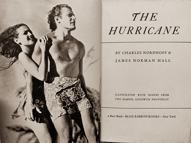 """Title page and frontispiece in """"The Hurricane"""" by Charles Nordhoff and James Hall. New York: Burt/Blue Ribbon Books, (1936). Movie scene with Dorothy Lamour as Marama and Jon Hall as Terangi."""