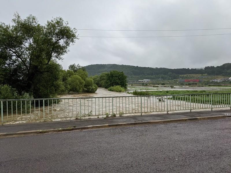 Flooded river rushing under bridge