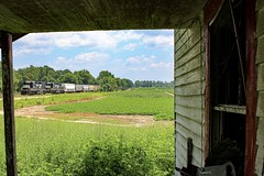 NS 152 with two SD40s passed by an abandoned house in South Georgia.