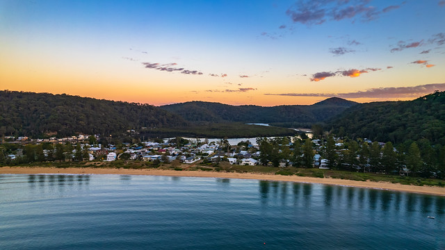 Peaceful sunrise over the bay with houses, river and mountains