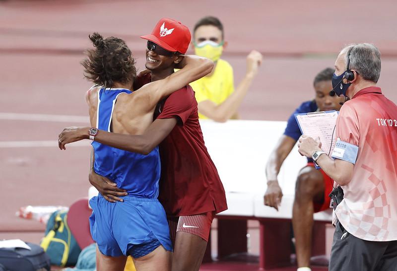 Gianmarco Tamberi(藍衣)與Mutaz Essa Barshim(紅衣)決定共享金牌後擁抱慶祝。(達志影像)
