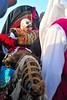 dans un silence religieux, la mariée émue arrive sur le dos d'un chameau impassible