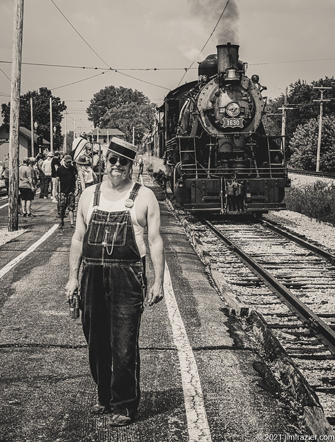 Man in Bib Overalls with Boater and Steam Engine
